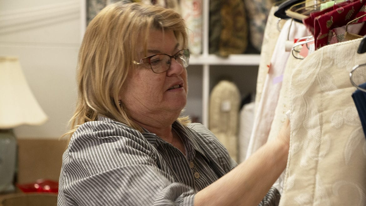Sheryl Raineri arranges clothing at the Manor Thrift Shop in Liberty, Missouri.