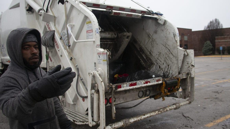 worker guiding motorist to trash truck