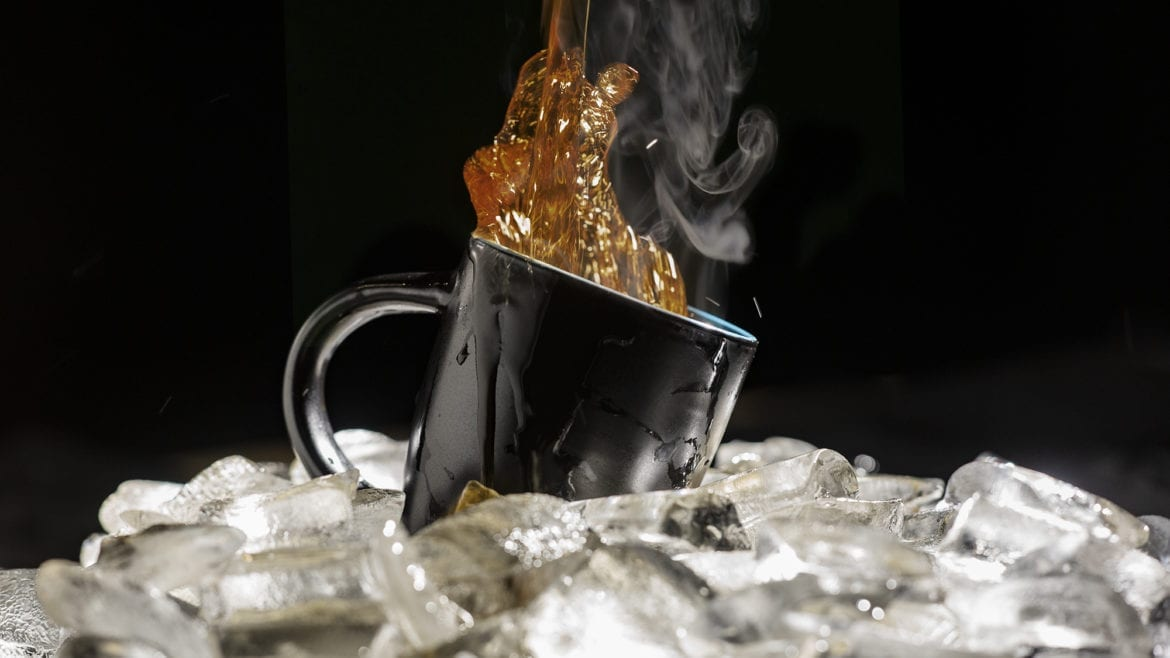 coffee pouring into a cup over ice