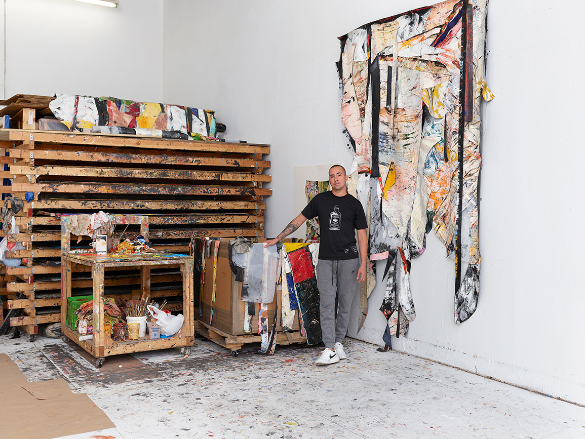 Angel Otero stands next to scrapped paintings