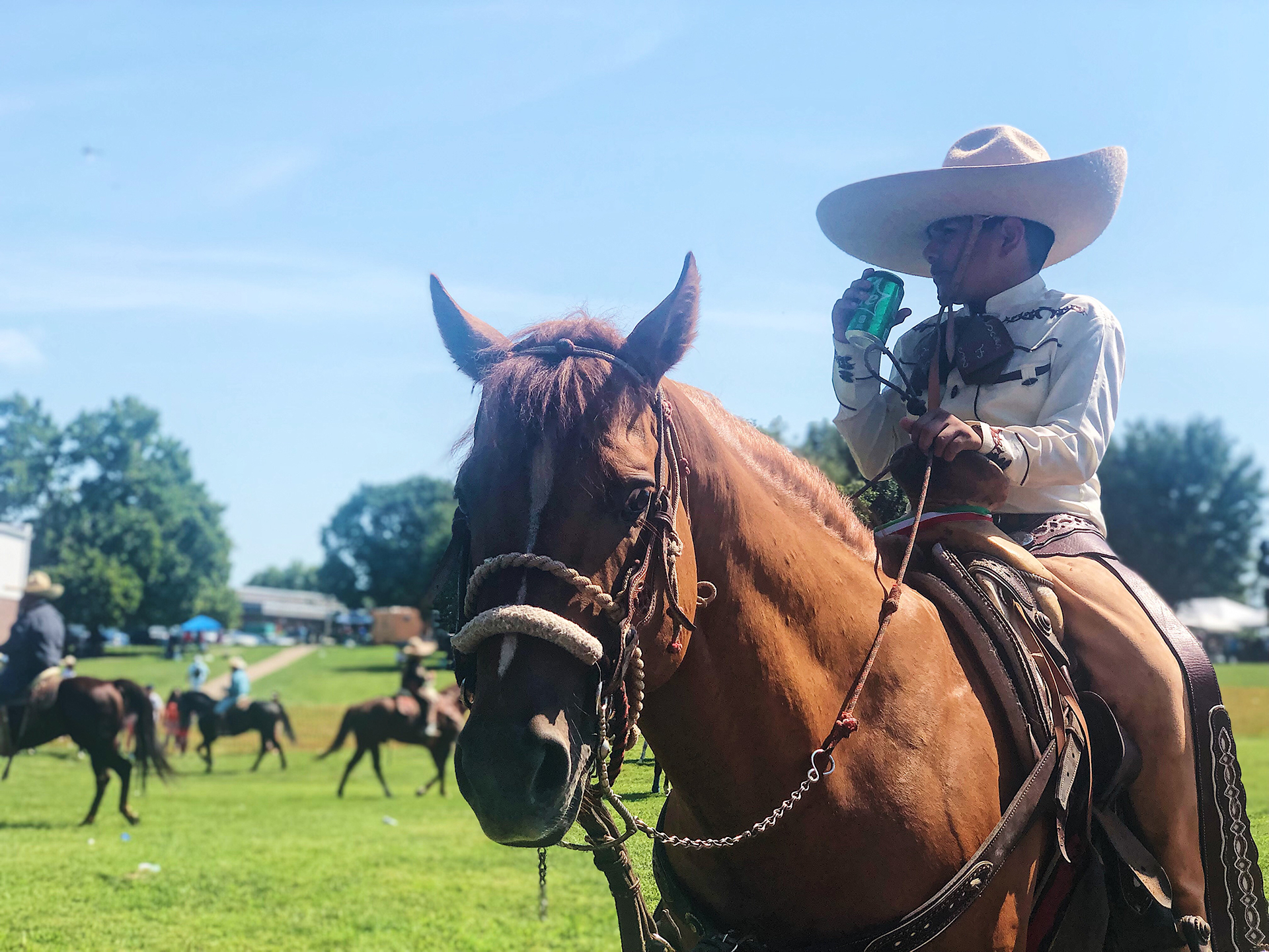 A boy on a horse with a cowboy hat clutches the saddle and sips a Sprite while taking a break during the Latino Arts Festival on Sept. 7. (Vicky Diaz-Camacho | Flatland)