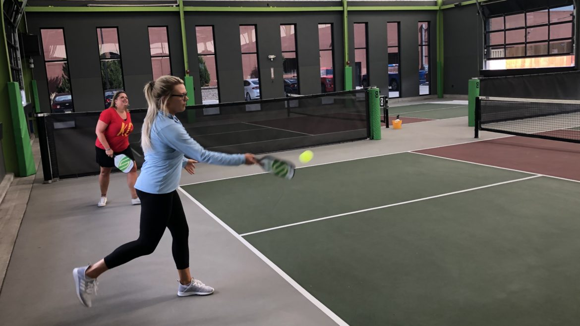 A woman serves the ball in a pickleball match.