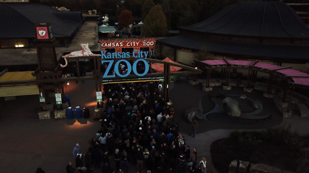 A crowd enters the zoo's front gate.