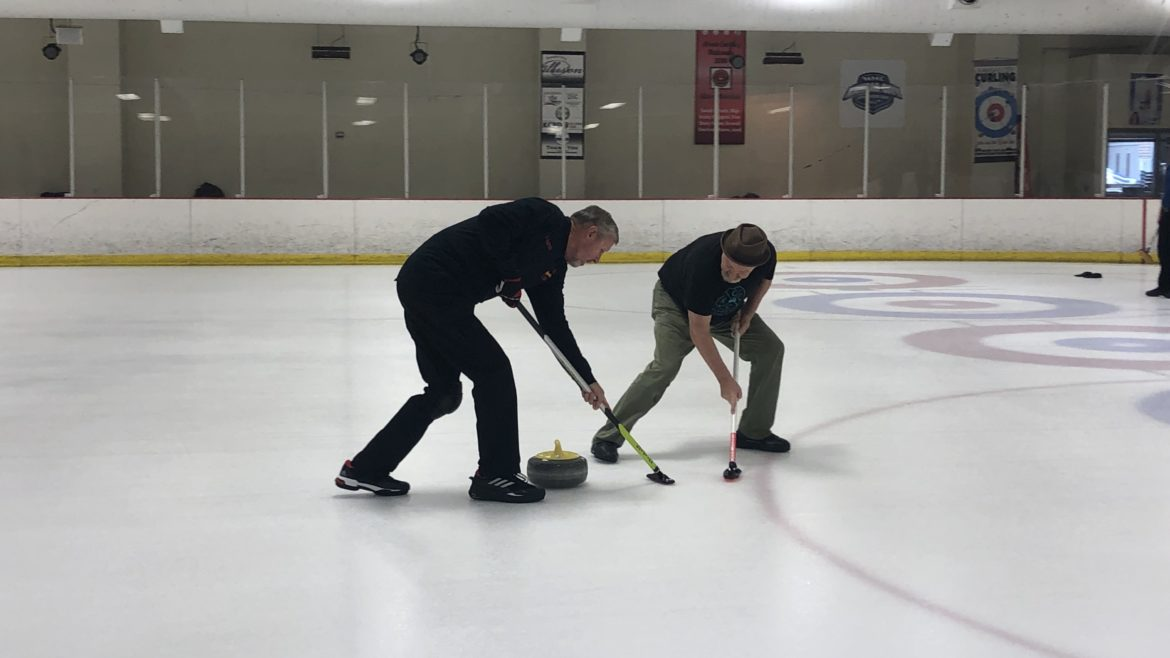 A pair of curlers sweep in front of the stone.