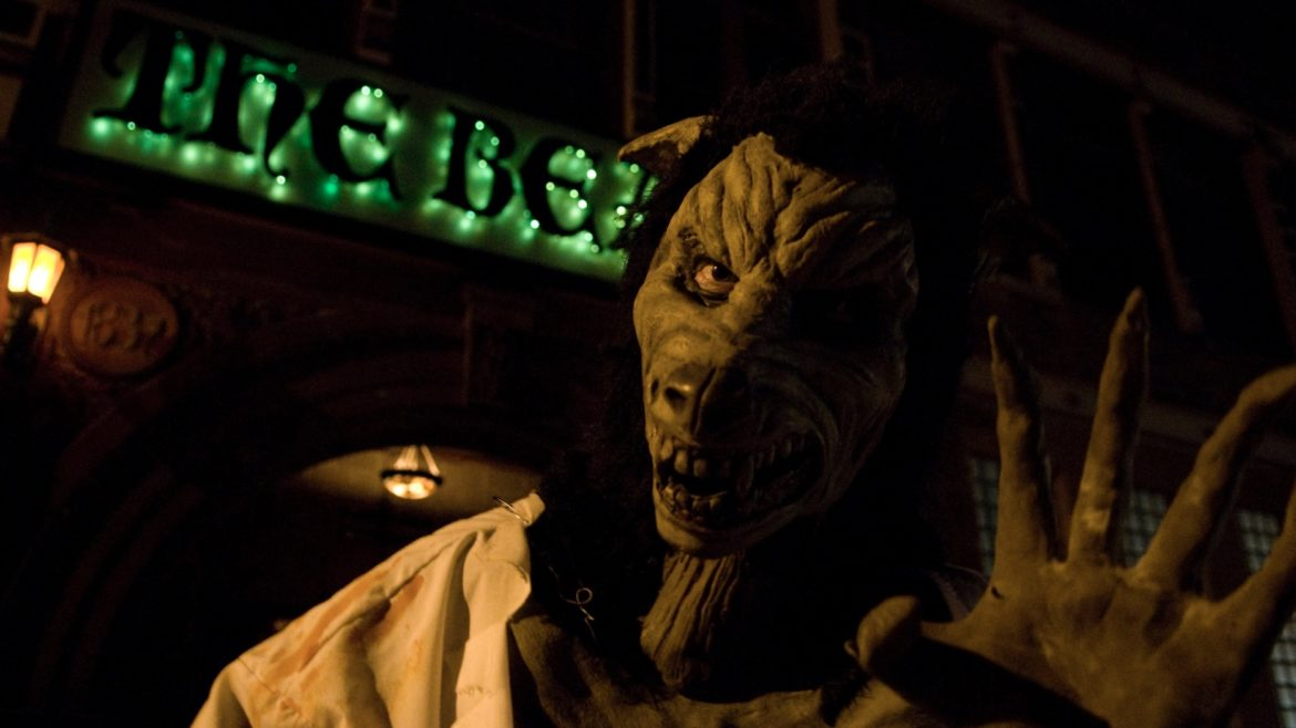 A beast-like creature waves at the camera in front of The Beast Haunted House.