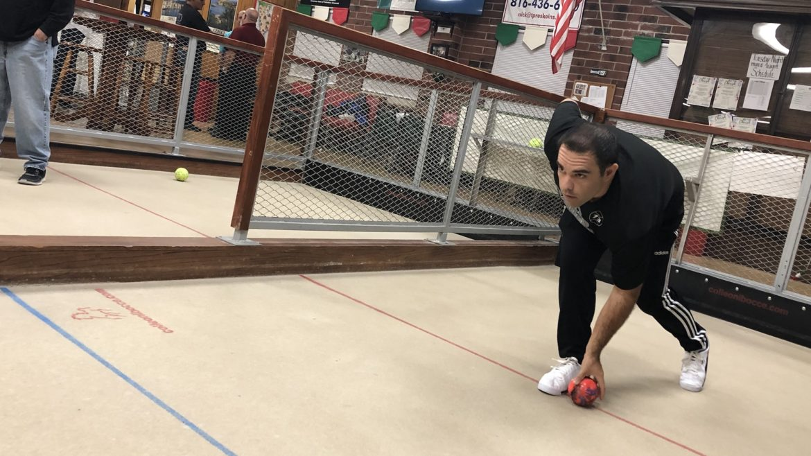 A man readies to roll his bocce ball.