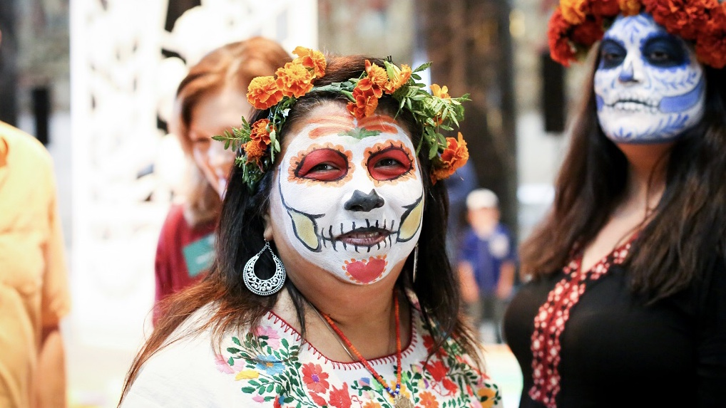 A woman poses in full calavera face paint.