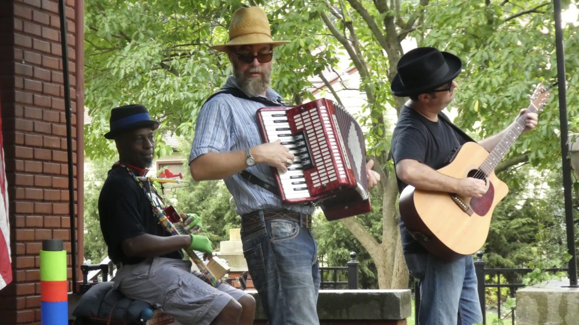 A man plays an accordion with his band.
