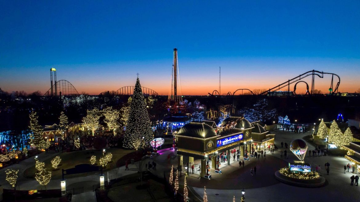 An aerial shot of Worlds of Fun lit up with Christmas lights at sunset.
