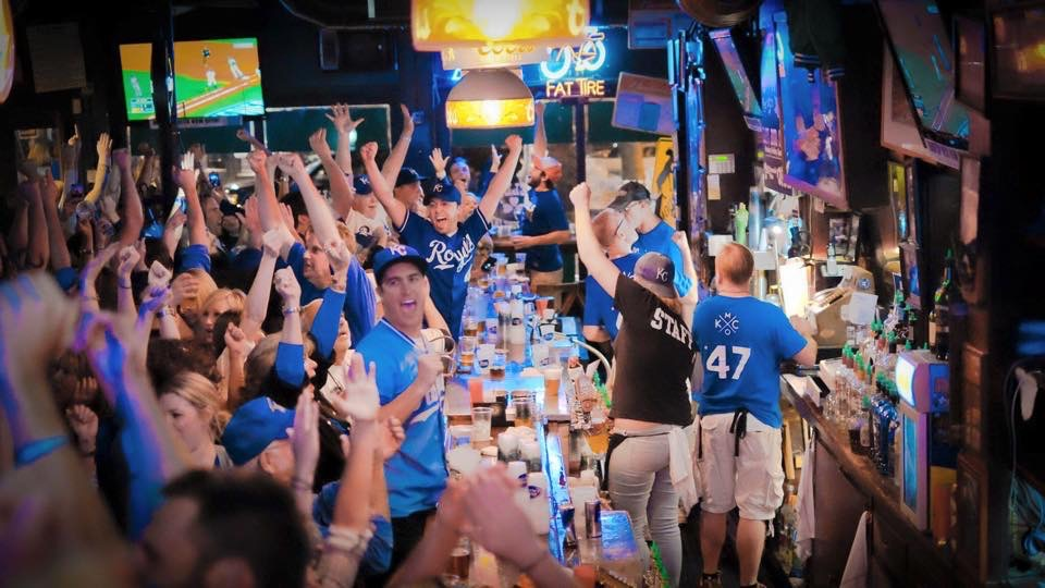 Fans celebrate in a crowded bar.