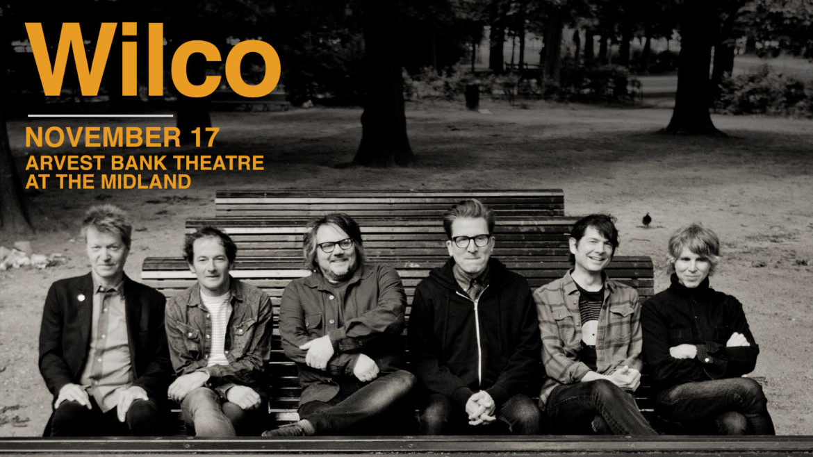 Members of Wilco sitting on a bench. Wilco is playing at The Midland November 17.