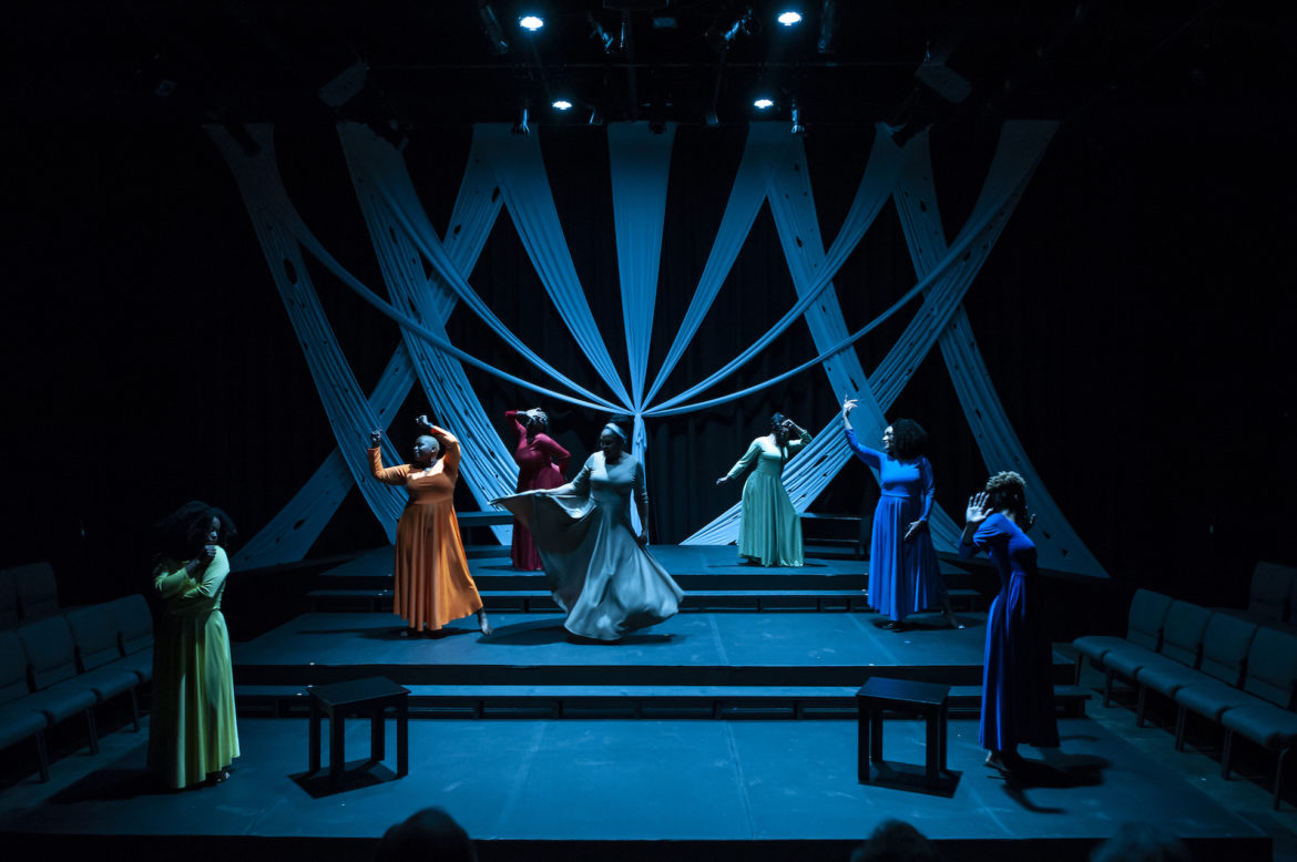 Seven women perform on a dim blue stage.