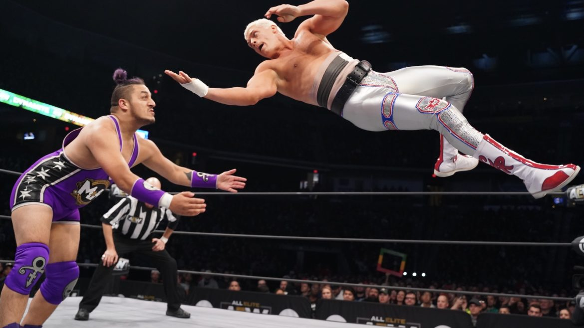 A wrestler jumps from the top rope towards an opponent.