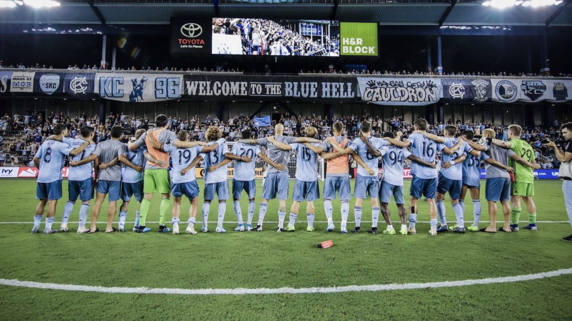 The Sporting Kansas City soccer team lines up and locks arms in front of the home crowd