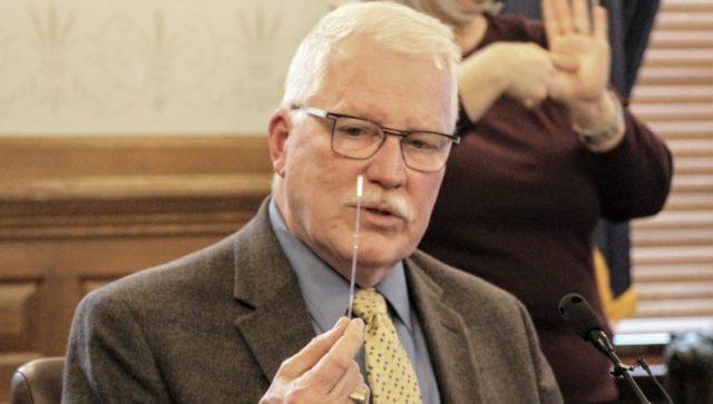 Kansas Health Secretary Lee Norman displays a swab used for COVID-19 testing.