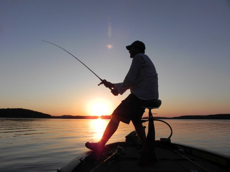 A fisherman at sundown on the lake.