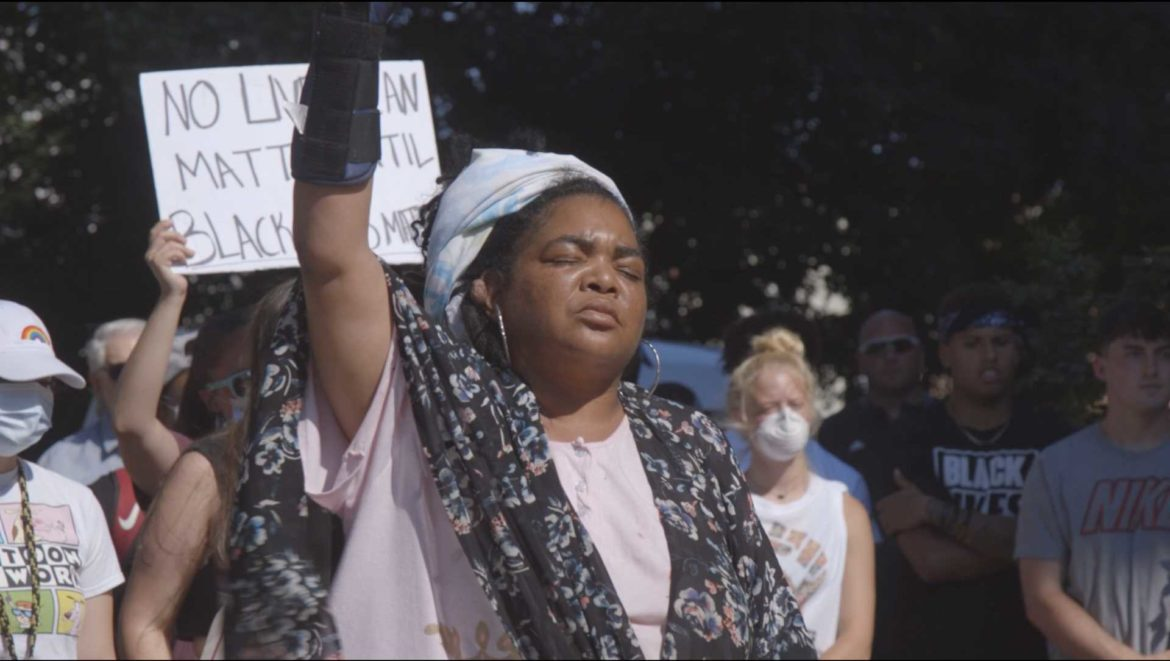 """A protester raises her fist during Reggie Palmer's speech at a """"Black Lives Matter"""" protest in Marshall, Missouri on Sunday, June 7, 2020."""