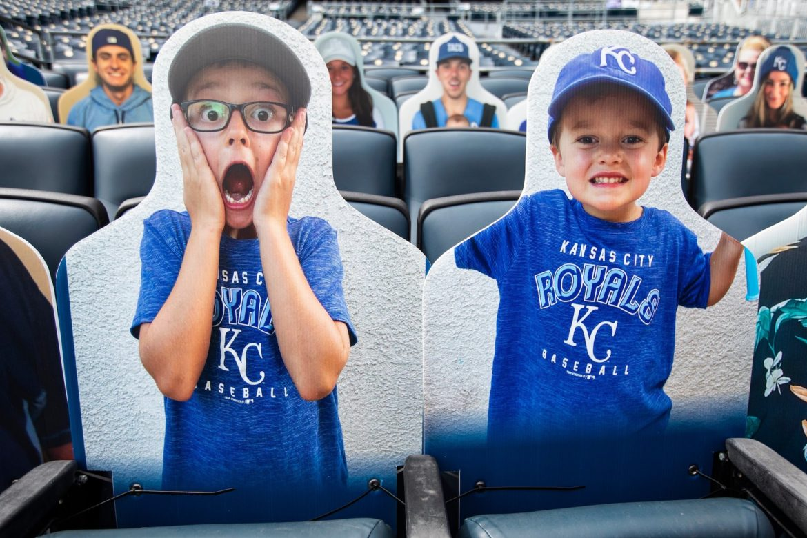 Two cardboard cutouts of fans resting in Kauffman Stadium's bleachers, ready for the home opener.