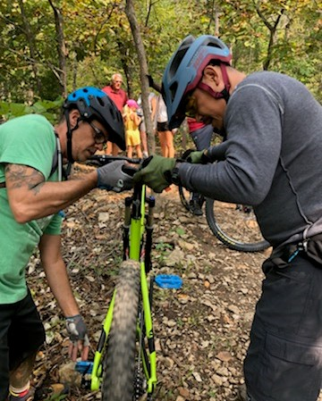 Chef Michael Foust of Black Sheep gets some adjustment help with his new mountain bike from Chef Anourom Thomson.