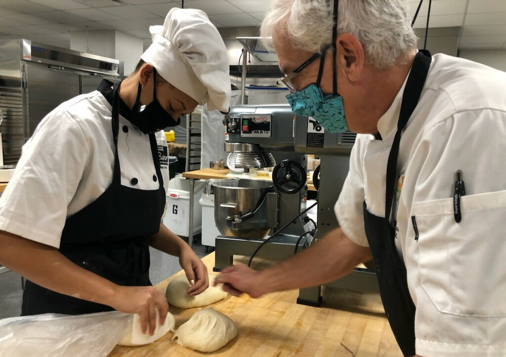 Culinary instructor Bob Brassard offers some hands-on baking instruction to Destany Moore.