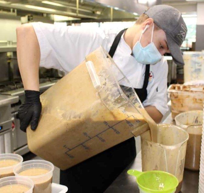 Noah Walls,17, pours gravy into quart containers.