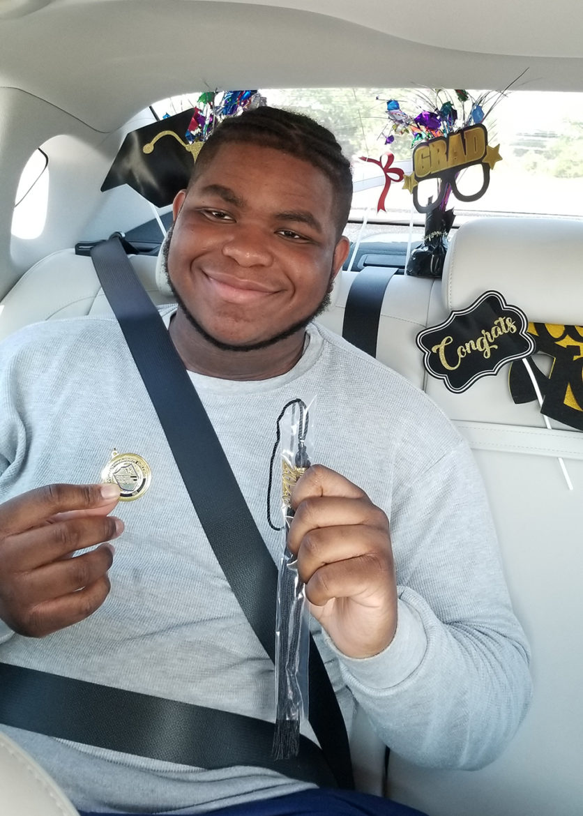Juleon Dillard, 19, smiles at his drive-through graduation, holding his tassel in one hand and a pin in the other