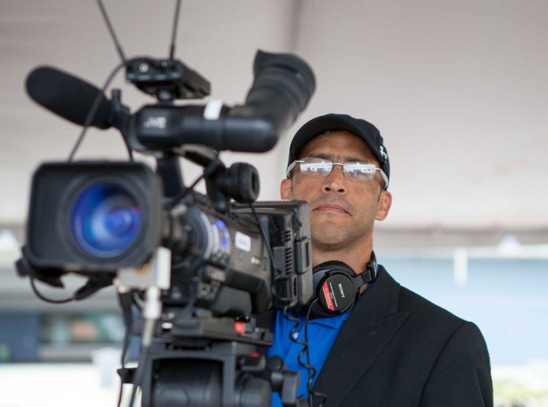Yosmel Serrano stands behind a camera.