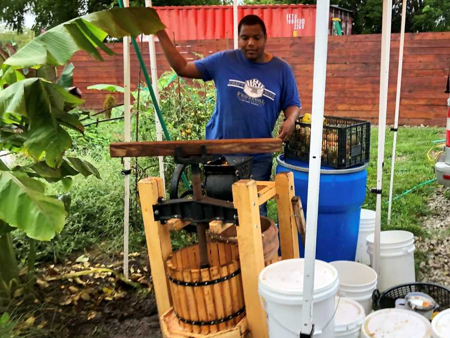 Eric Depradine presses apples at Of The Earth Farm + Distillery in Richmond, Missouri.