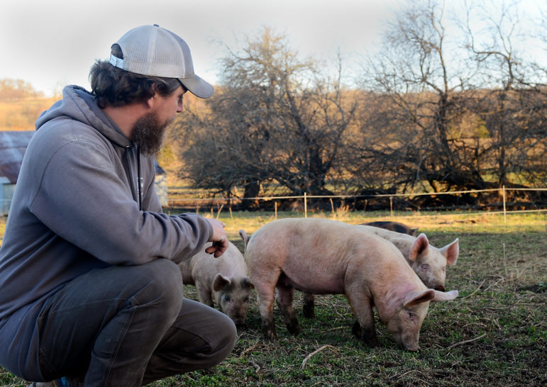 Andrew Geiser pets his pigs on Friday, March 19, 2021, in Chillicothe, Missouri.