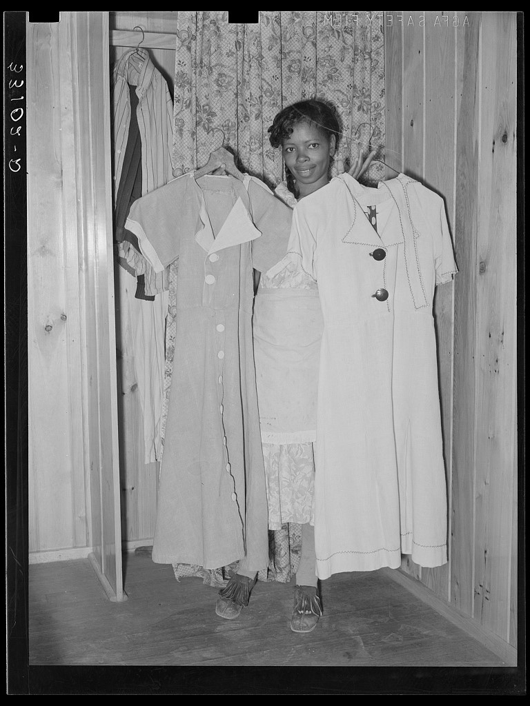 The wife of Farm Security Agent client holding dresses she made from flour sacks in Marshall, Texas, 1939.