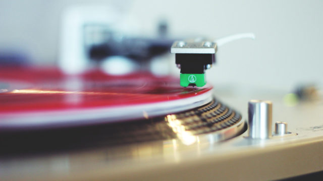 A red vinyl album spins on a turntable.