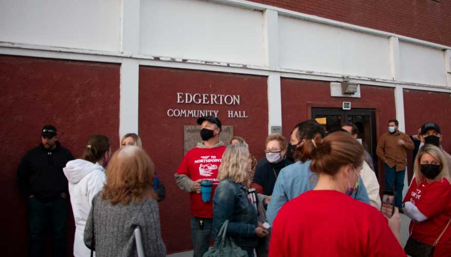 Area residents gather outside of the Edgerton Community Hall on March 11, 2021.