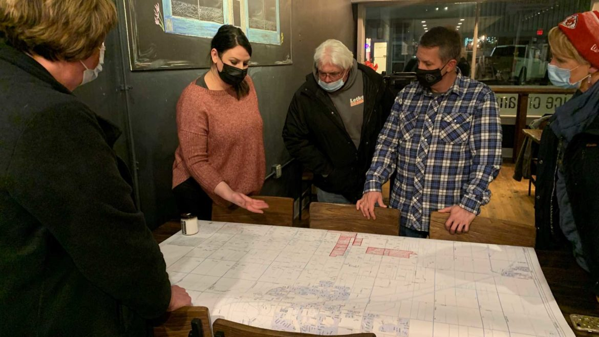 Jenni Koch shows other residents the parcels of land up for rezoning at The Coffee Bean Co. in Spring Hill, Kansas, on Feb. 9, 2021.