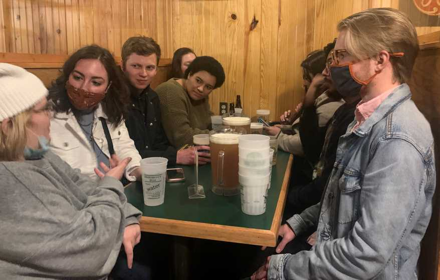 A group from the class of 2020 huddles around a small table at Shakespeare's Pizza on Friday, April 23, 2021.