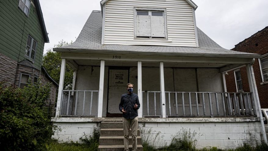 Gregg Lombardi stands in front of a home classified as a dangerous building in the Lykins Neighborhood of Kansas City, Missouri. The house is abandoned and situated in between two occupied homes.