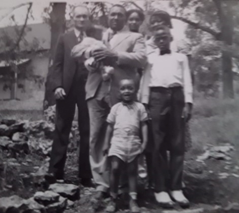 Herman Samuel Sears, Sr. (far left) and his wife, Almeda Pennington Sears (far right, back row) moved from Texas to Tulsa following the 1921 race massacre to help the community rebuild. In 1942 they joined other family members in Parkville, Missouri, for this family portrait, which included Frank Scott Douglass (holding his daughter Pearl) and his wife Lucille Sears Douglass, (to his left). Joining them was Charles Wesley Douglass, (front) son of Frank and Lucille, and Roscoe Turner, stepson of Lula Mae Turner, sister of Lucille.