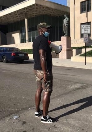 Steveland Young, with megaphone in hand, at one of the Friday night protests outside of Kansas City Police Department headquarters.