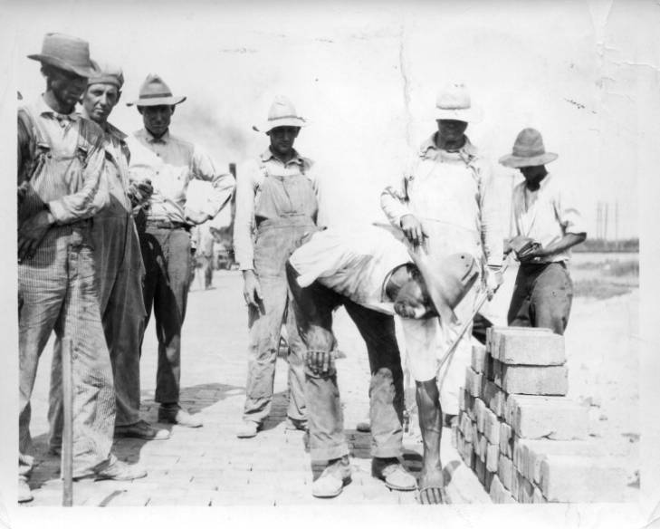 James Garfield Cleveland Brown lays bricks, surrounded by other brick road laborers. (Johnson County Museum)
