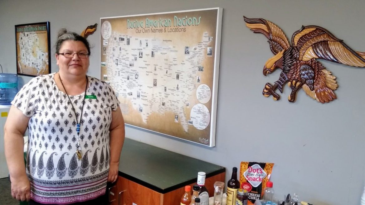 Gaylene Crowser, a member of the Standing Rock Sioux tribe, has been executive director of the Kansas City Indian Center for nine years. Behind her at the center is a map showing the location of some of the more than 500 federally recognized tribes of Indigenous people.