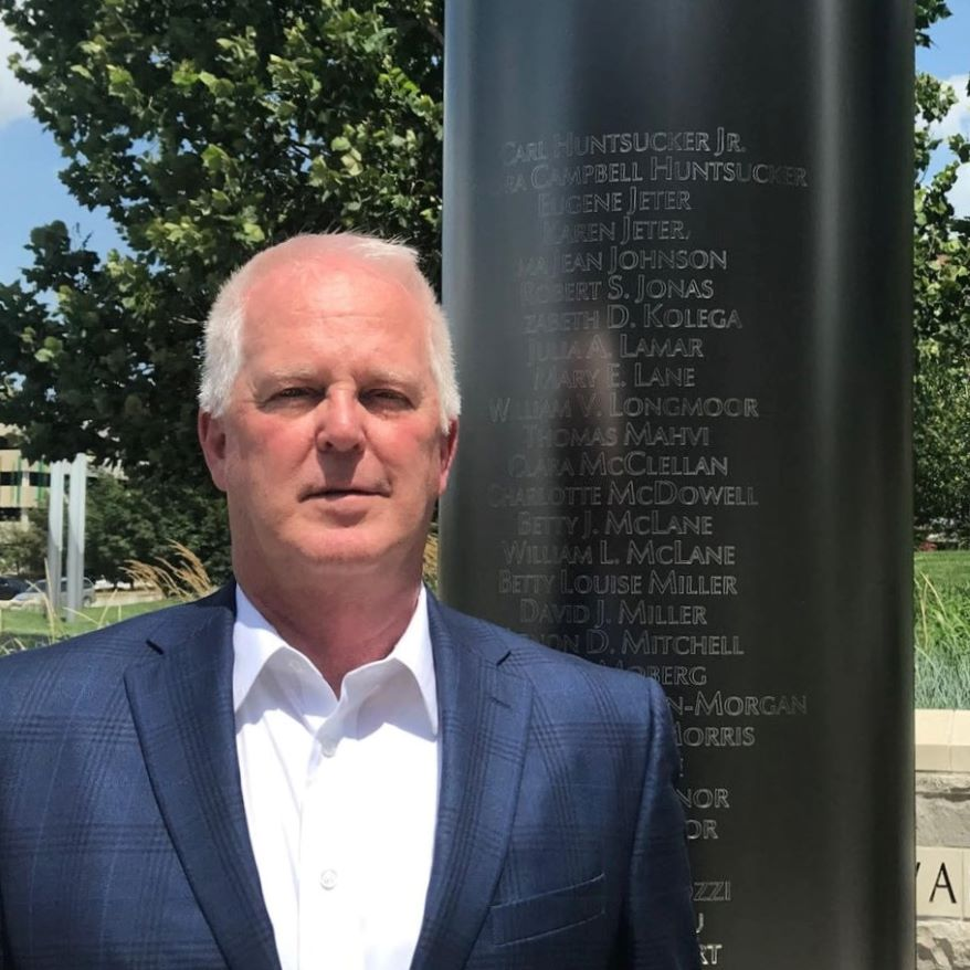 Brent Wright, who lost his mother and stepfather in the Hyatt skywalk collapse, poses next to the memorial listing the names of those who died in the disaster.