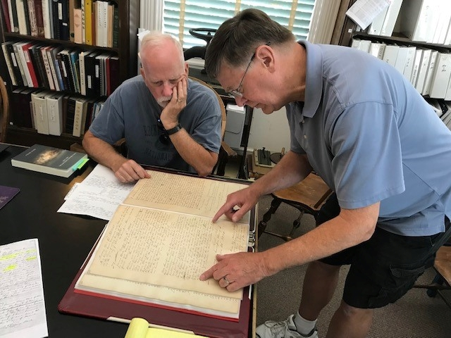 tephen Haymes, retired Clay County Circuit Court clerk (left) and Tony Meyers, Clay County Archives & Historical Library president, examine a court ledger book which contains the 1841 conclusion of a formal court partitioning of four enslaved people among several owners.