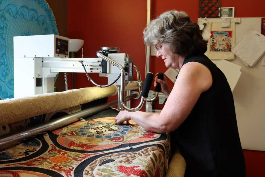 Robyn Gragg uses her long-arm sewing machine to make intricate quilting designs. Robyn Gragg uses her long-arm sewing machine to make intricate quilting designs.