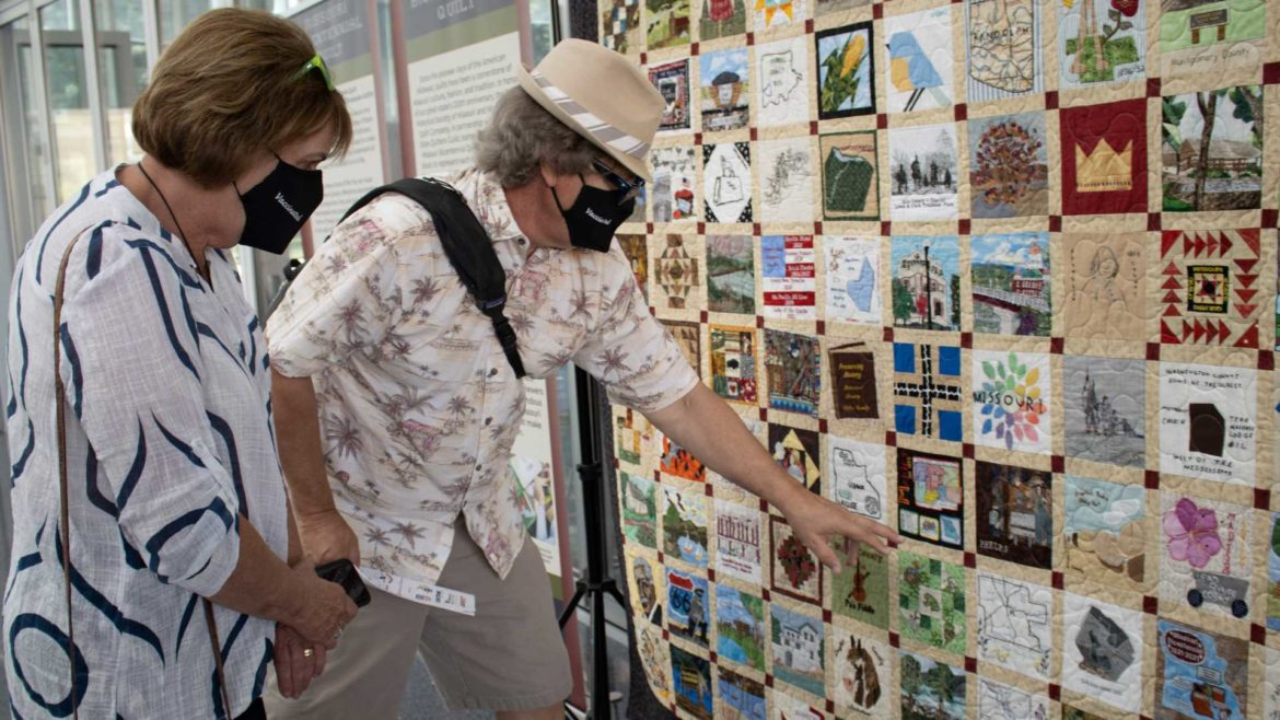 Steve and Calene Cooper identify blocks and stories shown in the Missouri Bicentennial Quilt.