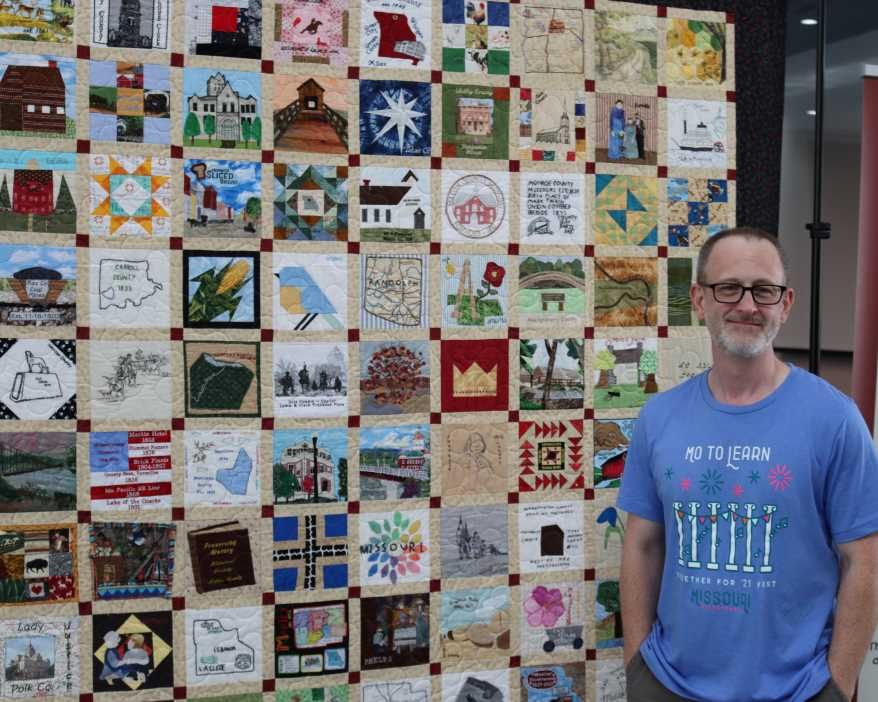 Michael Sweeney has driven the Missouri Bicentennial Quilt all around the state to make sure everyone can see it. Here he stands next to it at its exhibition in Columbia, Missouri.