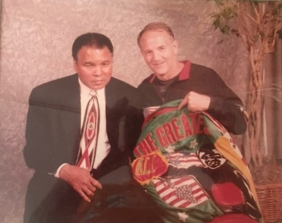 """During Muhammad Ali's visit to Kansas City in 2000, Kansas City area boxing coach and trainer John Brown presented him with a jacket bearing the words """"Greatest Of All Time."""""""