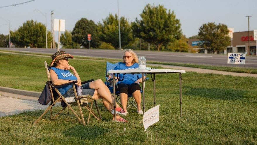 Two volunteers sit at a booth collecting signatures to recall 4th Councilman Eric Bunch. The recall attempt was unsuccessful.