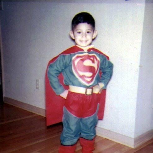 Velasquez as a child, posing dressed as Superman
