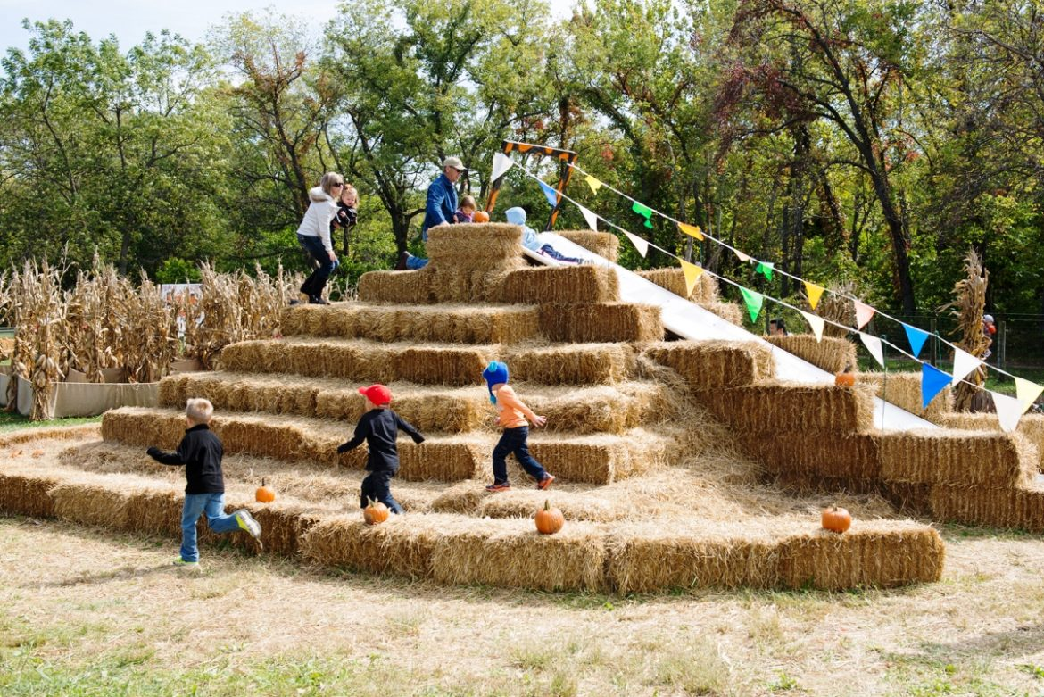 Kids playing on a large pyramid of hay.